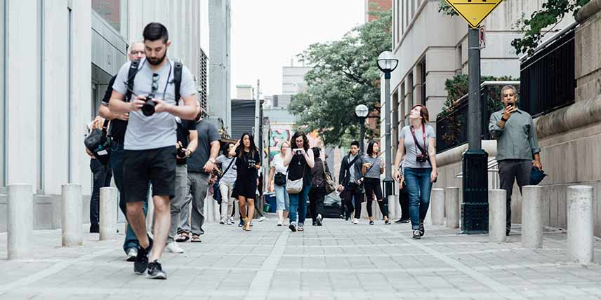 Image of people walking in street distracted by digital devices