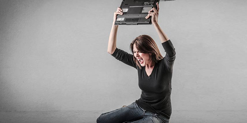 A frustrated woman holds her laptop computer above her head