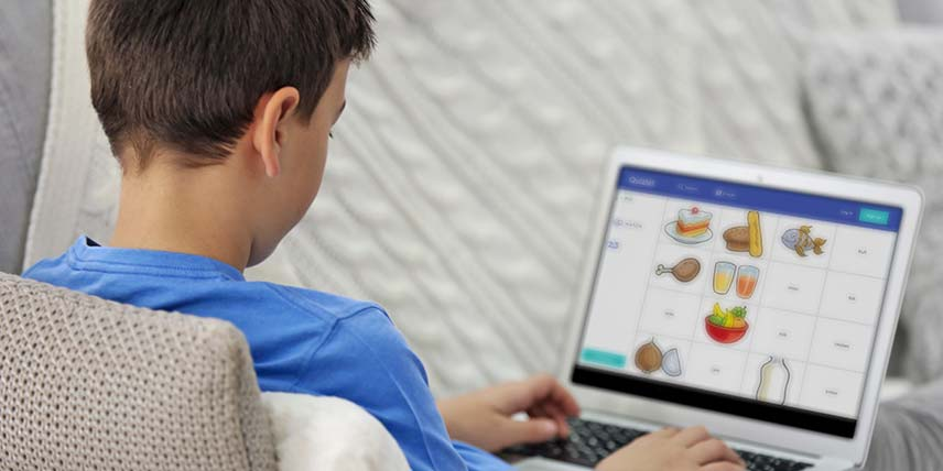 A boy sits on a sofa using a tablet to match pictures of food and their names