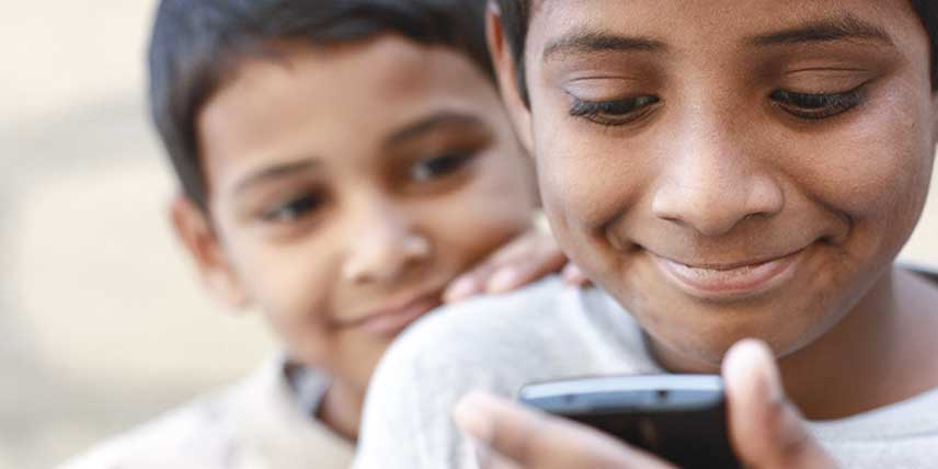 Two boys look at a mobile phone