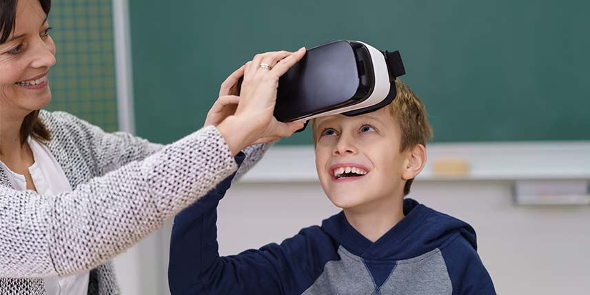 A young boy smiles as his teacher helps him put on a VR headset