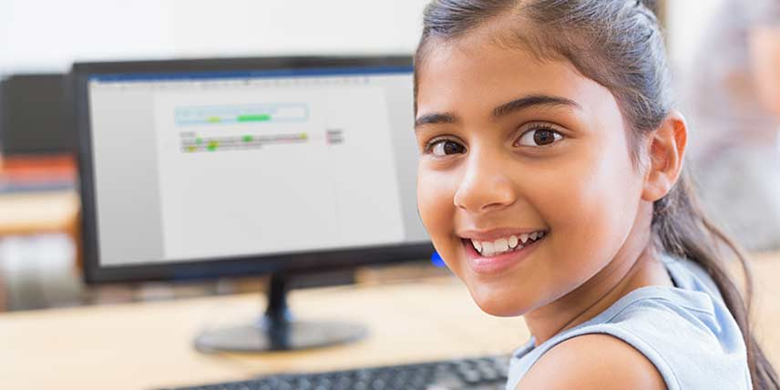 A girl using a desktop computer turns to smile at the camera