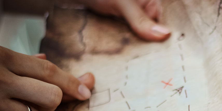A person's hands holding an old treasure map