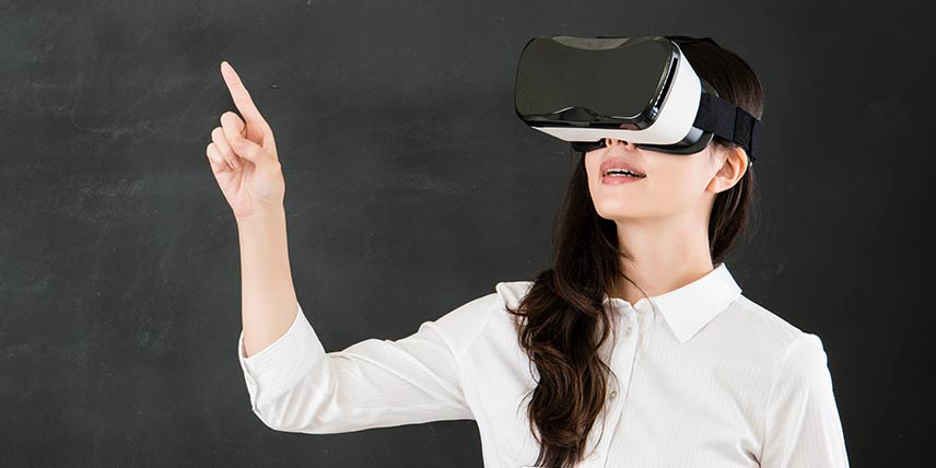 A woman with a VR headset on looks up and points