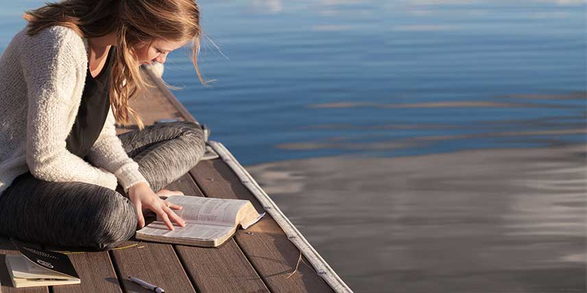A woman sitting on a pier reading a book