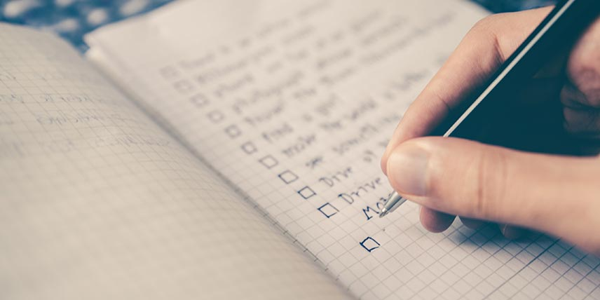 A notebook showing a hand adding to a written checklist