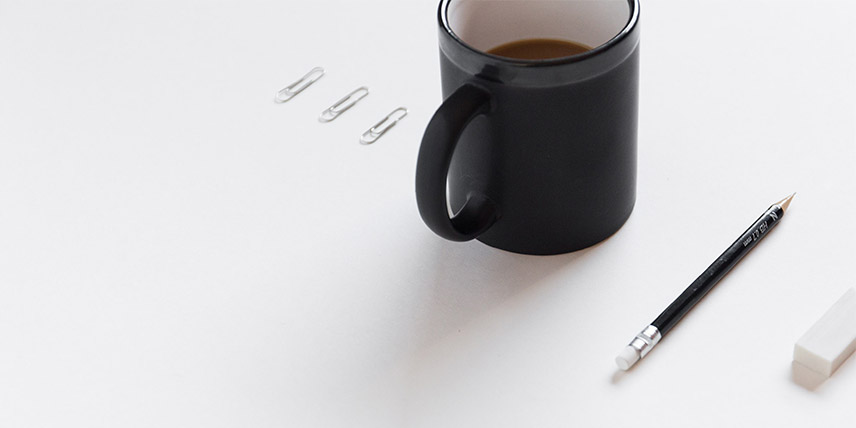 A mug of coffee, three aligned paperclips and a pencil on a white background